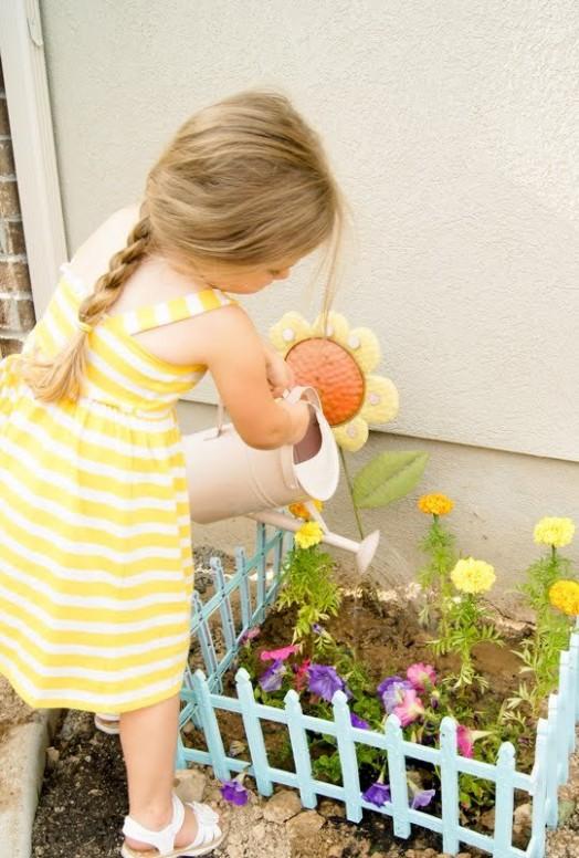 ילדה משקה פרחים